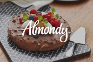 Almondy chocolate frozen Swedish tarte displayed on slate board and silver cake slicer with Almond logo overlayed