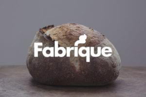 Fabrique white logo overlayed on fresh bread