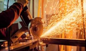 Man in workshop using chopsaw to cut through metal length with sparks flying