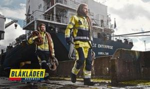 Workmen holding hoses are walking down the side of a Gibraltar ship wearing Blaklader workwear