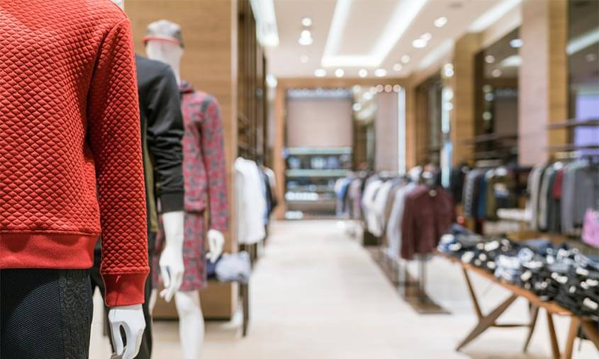 Clothing shop with mannequin in shot wearing red quilted jumper and black denim style jeggings and clothes rails and trestle table with items spread on display