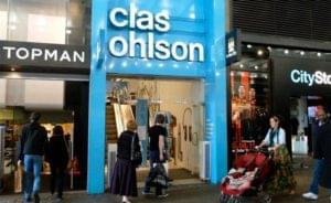 High street Clas Ohlson store front with distinctive blue and white brand logo with shoppers to the front browsing items