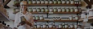 Business owner holding jar of food seasoning stood in front of larder shelving