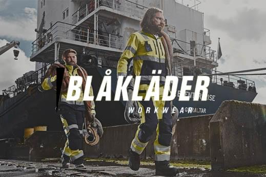 Blaklader hi-vis jacket and trouser workwear being modelled with two people carrying hoses and equipment from a ship