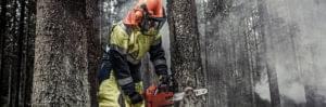 Blaklader worker demonstrating protective workwear, ear defenders, helmet, and mask whilst using tree cutter to cut a tree down