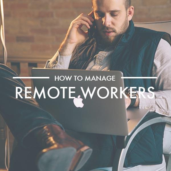 Man sat with Apple laptop on the phone working from a remote location