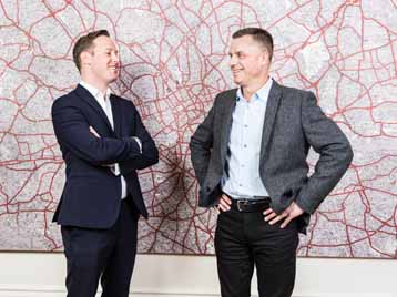 Alexander and Kevin in Goodwille London office with arms crossed in front of a map