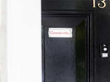 Goodwille sign on black front door to the office